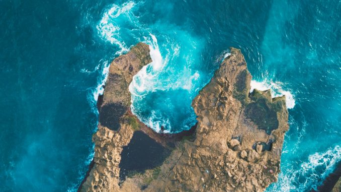photo of brown rocks between blue body of water by deb1909 (Unsplash.com)
