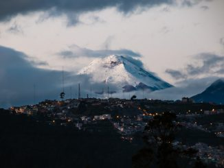 town with lights far from mountain field with snow by multimaniaco (Unsplash.com)