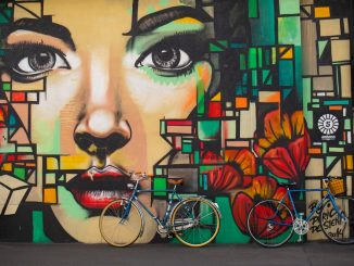Bikes lean against wall painting by timon_k (Unsplash.com)