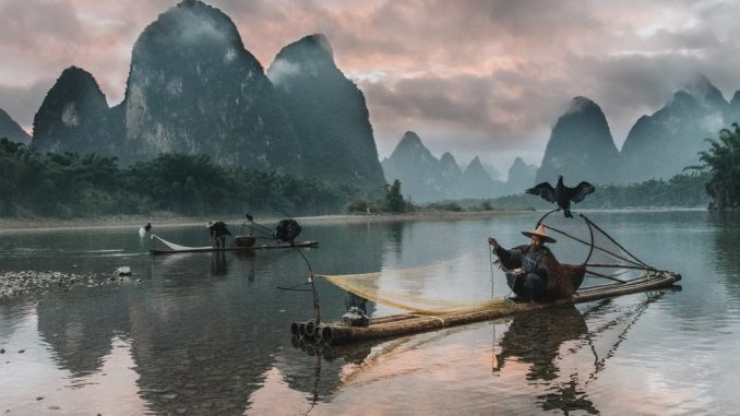 Sunset on the Li River as the few remaining cormorant fisherman pack their nets for the night. by sam_beasley (Unsplash.com)